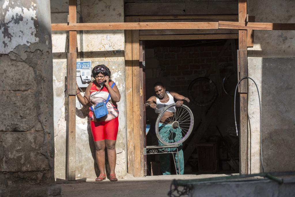 A woman speaks on a public telephone as a man repairs a wheel in Havana, Cuba, Saturday, Nov. 26, 2016, the day after Fidel Castro's de...