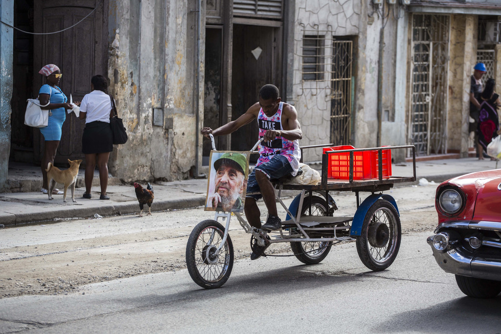 A man rides his tricycle decorated with a picture of Fidel Castro, one day after Castro died in Havana, Cuba, Saturday, Nov. 26, 2016. ...