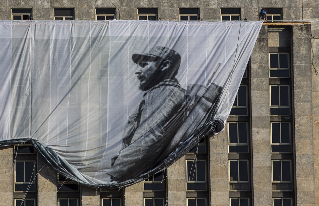 Men hang a giant banner with a picture of Cuba's late leader Fidel Castro as a young revolutionary, from the Cuban National Library bui...