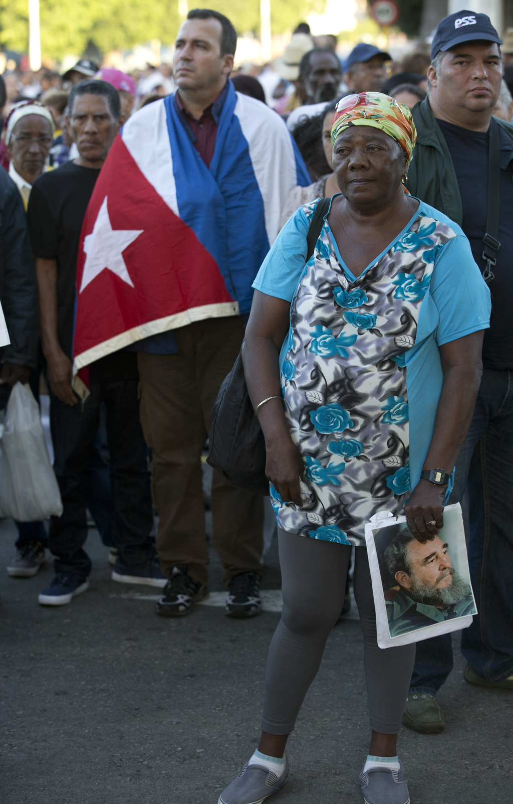 A woman holds an image of the late Fidel Castro as she waits to enter Revolution Plaza, the site of two days of tributes to Castro, in ...
