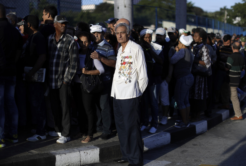 Mourners wait in line to enter Revolution Plaza, the site of two days of tributes to the late Fidel Castro, in Havana, Cuba, Monday, No...