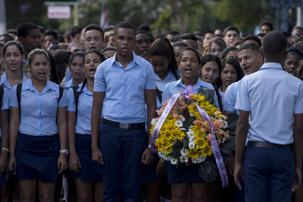 Students march, one carrying a wreath, to a memorial honoring the late Fidel Castro, in the Ciudad Escolar Libertad neighborhood in Hav...