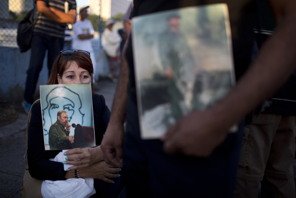 A woman holds an image of the late Fidel Castro as she waits in line to pay her final respects to the late leader, in Havana, Cuba, Mon...