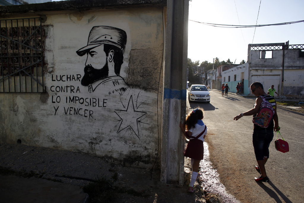 """A man walks his daughter from school past a mural of the late Fidel Castro, flanked by a quote from Castro that says in Spanish: """"Fight..."""