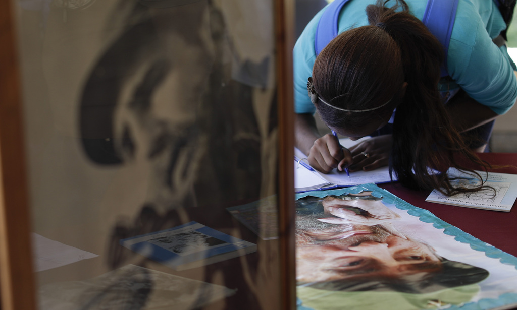 A woman signs a book of condolences for Cuba's late leader Fidel Castro at the  President Salvador Allende School, in Havana, Monday, N...