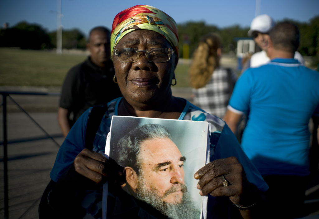 A woman holds an image of Fidel Castro as she waits in line to pay her final respects to the late leader, in Havana, Cuba, Monday, Nov....