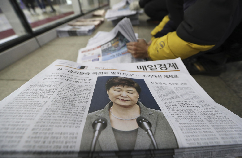 A worker prepares to deliver newspapers reporting on South Korean President Park Geun-hye's public announcement at a distrobution stati...