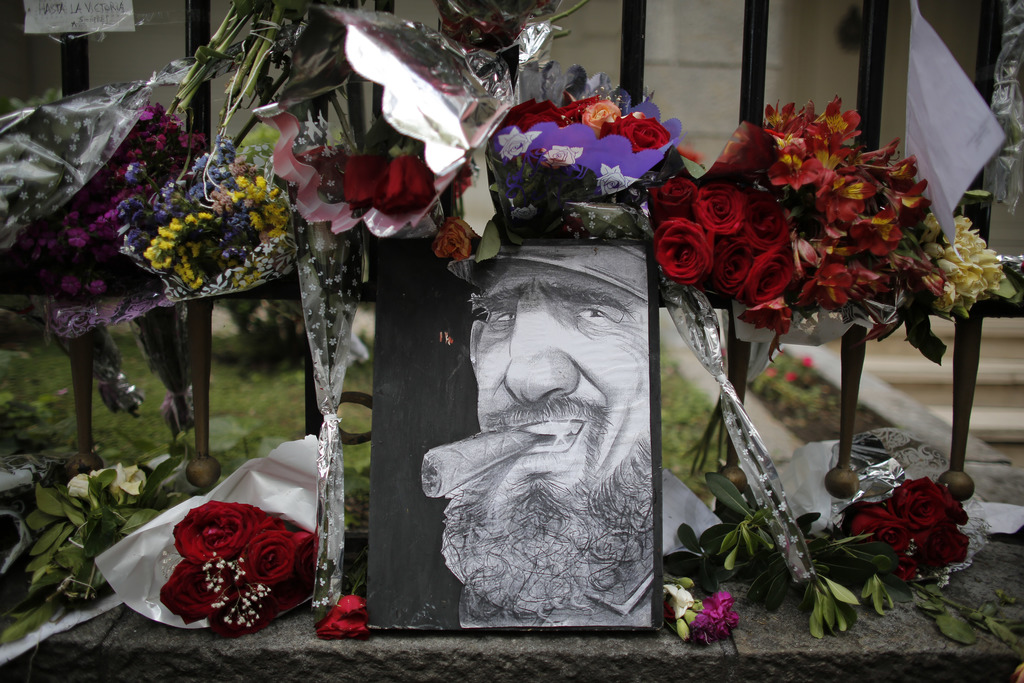 A caricature depicting Cuba's late leader Fidel Castro is surrounded by flowers at a makeshift memorial outside the Cuban embassy in Bu...