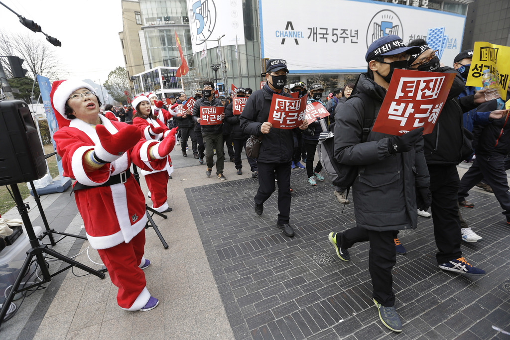 Protesters pass street performers dressed in Santa suits as they march during a rally calling for South Korean President Park Geun-hye ...