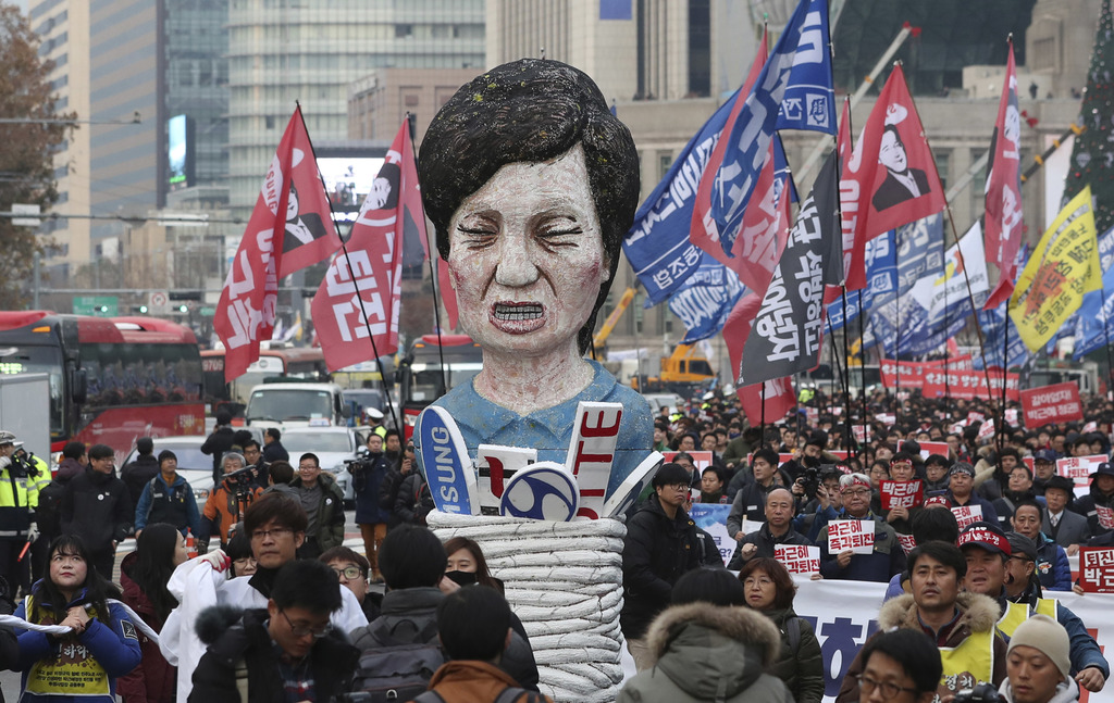 Members of the Korean Confederation of Trade Unions carry an effigy of South Korean President Park Geun-Hye as they march during a rall...