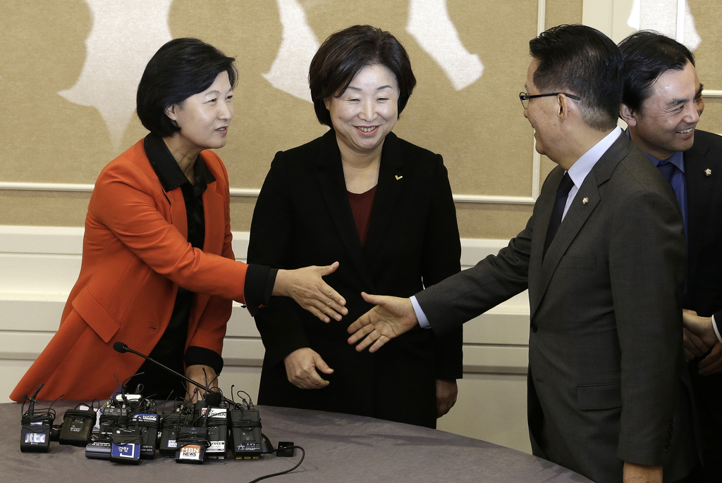 Choo Mi-ae, left, leader of the main opposition Democratic Party, shakes hands with Park Jie-won, interim leader of the People's Party,...