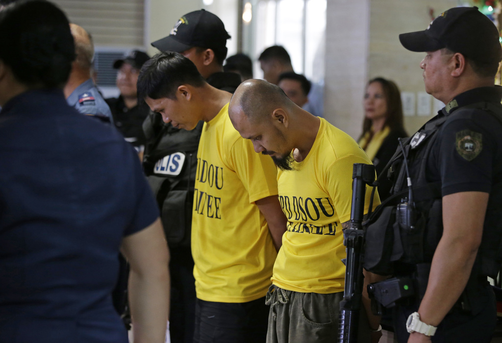 Suspected bombers, Jiaher Guinar, center left, and Rashid Kilala, center right, as are presented to reporters at police headquarters in...