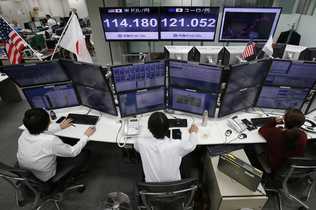 A monitor shows the current exchange rate between Japanese yen and U.S. dollar, rear left, and between yen and euro, rear right, at a f...