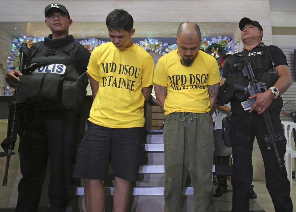 Police secure suspected bombers, Jiaher Guinar, center left, and Rashid Kilala, center right, as they are presented to reporters at pol...