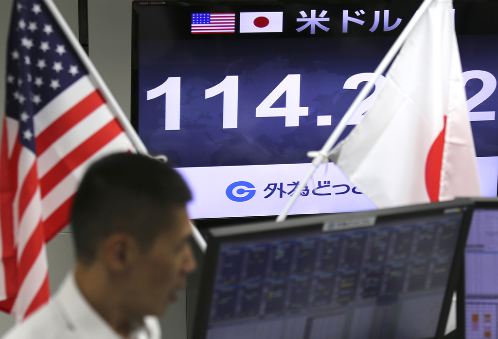 A monitor shows the current exchange rate between Japanese yen and U.S. dollar, top, at a foreign exchange brokerage in Tokyo Thursday,...