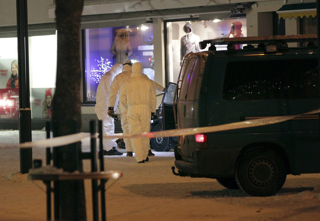 Police investigate the area where three women were killed in a shooting incident outside of a restaurant in Imatra, Finland after midni...