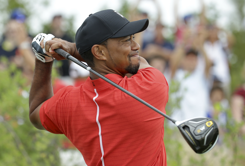Tiger Woods watches his tee shot on the first hole during the final round at the Hero World Challenge golf tournament, Sunday, Dec. 4, ...