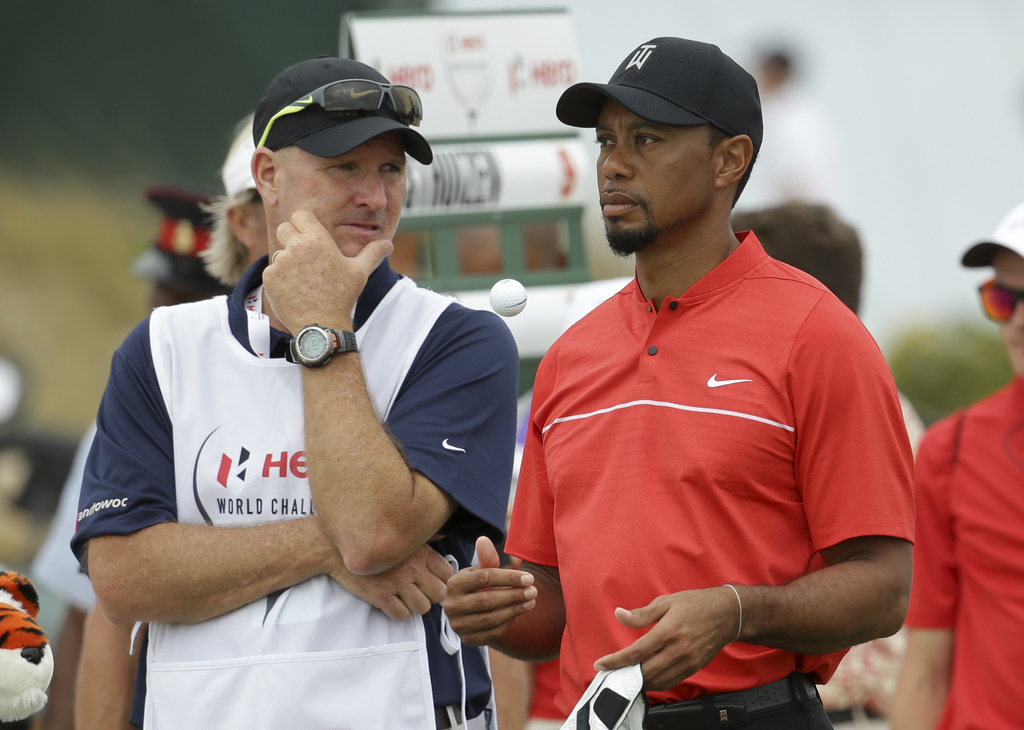 Tiger Woods waits with his caddie, Joe LaCava, to tee off on the second hole during the final round at the Hero World Challenge golf to...