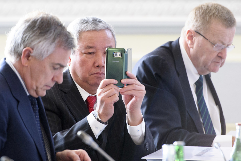 International Olympic Committee, IOC, Vice President Zaiqing Yu, center, from China, looks at his mobile phone next to Vice President J...