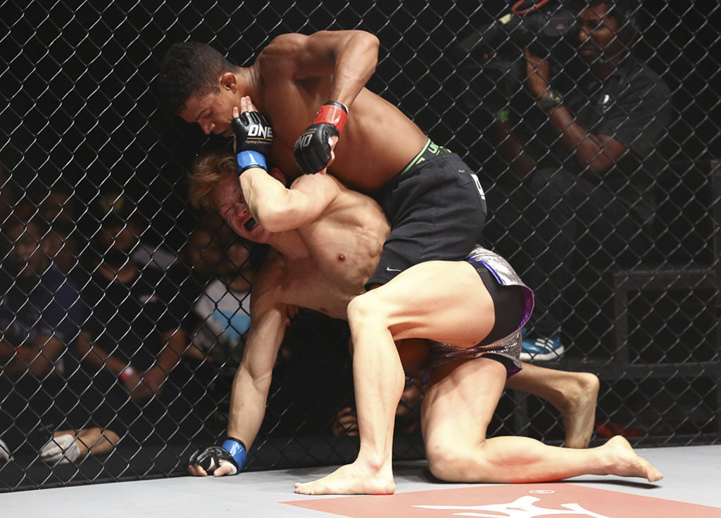 In this March 13, 2015 photo, Adriano Moraes punches opponent Riku Shibuya during a MMA competition in Kuala Lumpur, Malaysia. Asia's l...