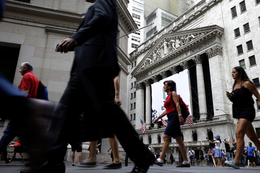 FILE - In this Monday, Aug. 24, 2015, file photo, people walk past the New York Stock Exchange. Congress is looking for ways to raise revenue, and one...
