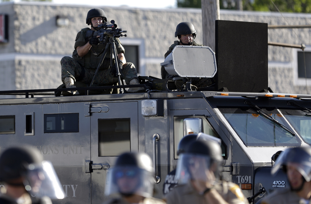 In this Aug. 9, 2014, file photo, a police tactical team moves in to disperse a group of protesters following the shooting of a young b...
