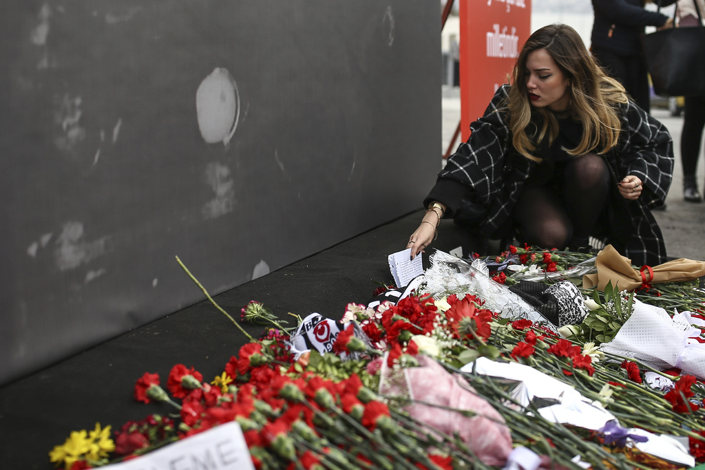 A Turkish woman leaves a message outside the Besiktas football club stadium Vodafone Arena in Istanbul, Monday, Dec. 12, 2016. Turkey l...