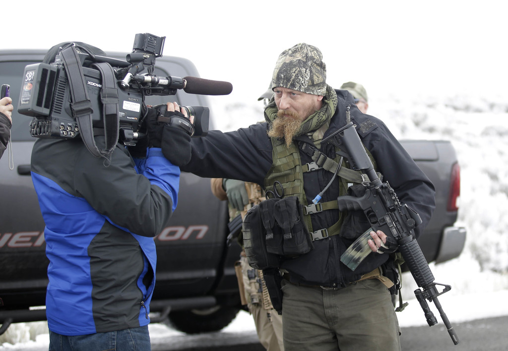 """FILE - In this Saturday, Jan. 9, 2016 file photo, a armed man pushes a videographer aside after members of the """"3% of Idaho"""" group, alo..."""