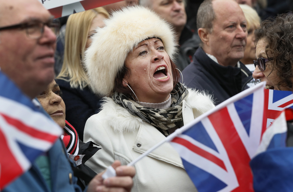 FILE - In this Wednesday, Nov. 23, 2016 file photo, pro-Brexit demonstrators wave flags outside the Parliament in London. The protest w...