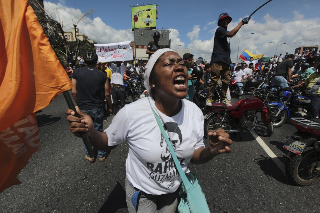 FILE - In this Thursday, Sept. 1, 2016 file photo, a demonstrator shouts insults against President Nicolas Maduro during a protest in C...