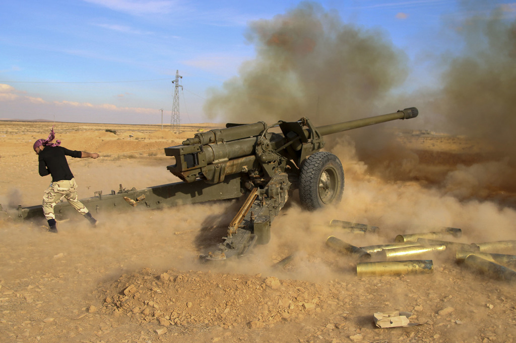 FILE - In this Saturday, Jan. 30, 2016 file photo, Syrian government troops fire at Islamic State group positions near Mahin, Syria. As...