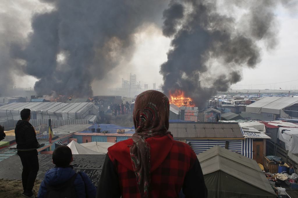 FILE - In this Wednesday, Oct. 26, 2016 file photo, people stand on a hill as smoke and flames rise from amidst tents, after fires were...