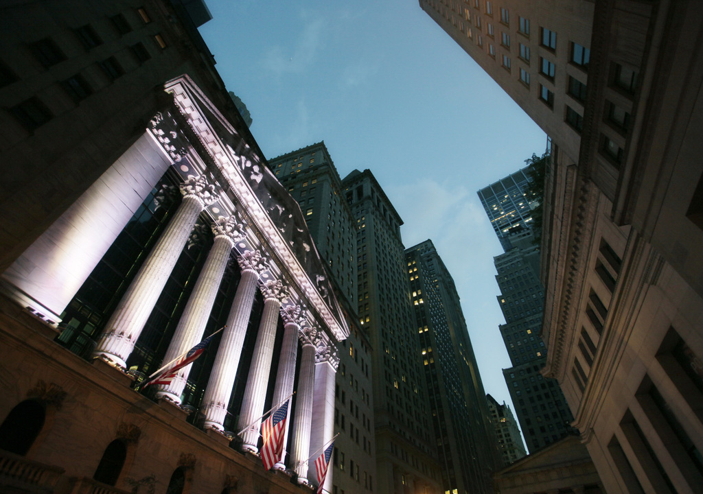 FILE - In this Wednesday, Oct. 8, 2014, file photo, American flags fly in front of the New York Stock Exchange. World stock markets were mixed on Thur...