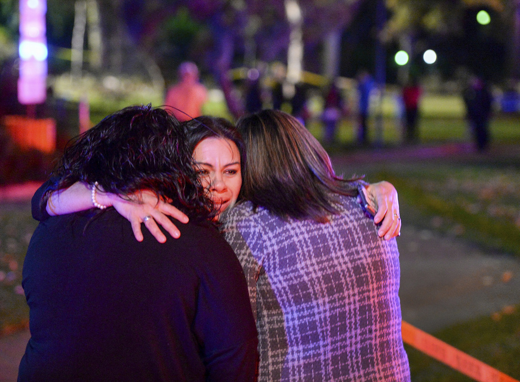 People close to the wedding party embrace as Los Angeles County Fire Dept. firefighters work at the scene where a large tree fell on a ...