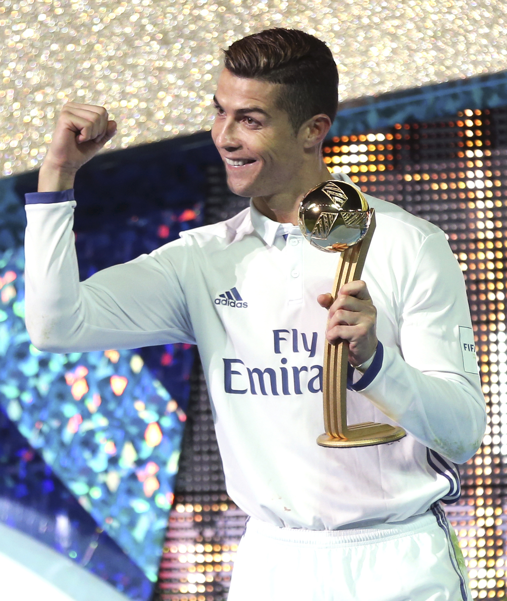 Real Madrid's Cristiano Ronaldo poses with the trophy for a photo after beating Kashima Antlers 4-2 to win the FIFA Club World Cup socc...