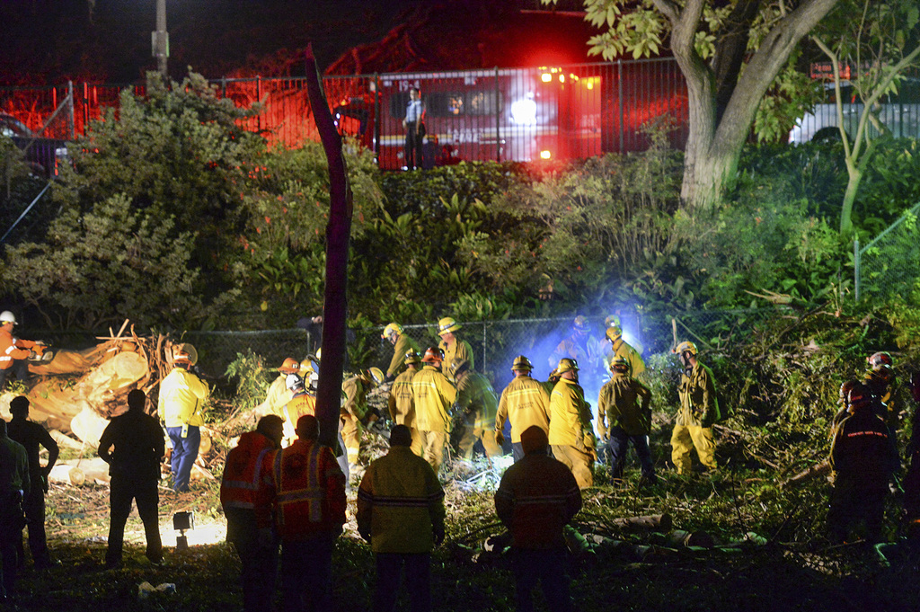 Los Angeles County Fire Dept. firefighters work at the scene where a large tree fell on a wedding party in Whittier, Calif., Saturday, ...