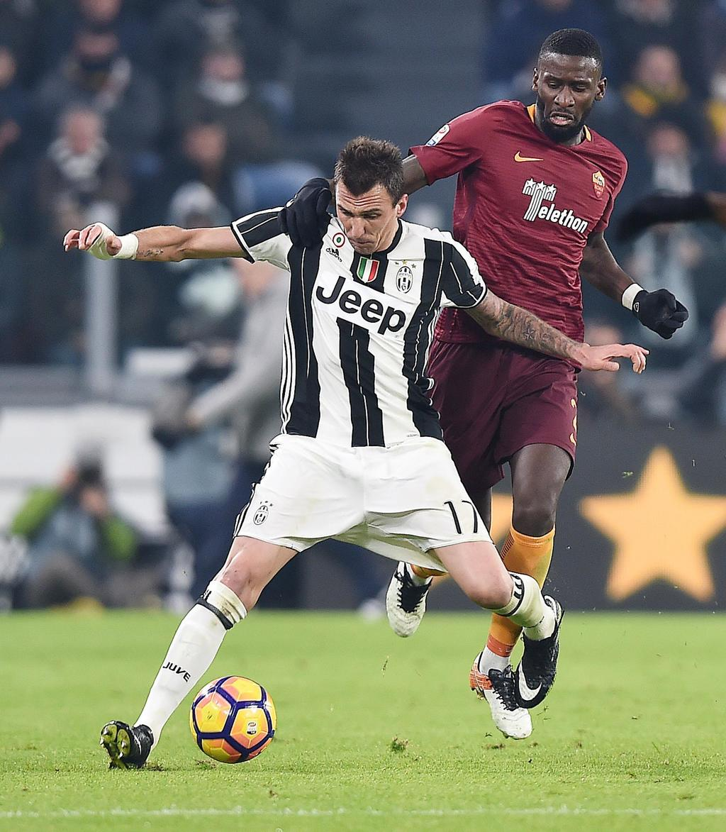 Juventus' Mario Mandzukic, left, is challenged by Roma's Antonio Rudiger during a Serie A soccer match, at the Juventus Stadium in Turi...