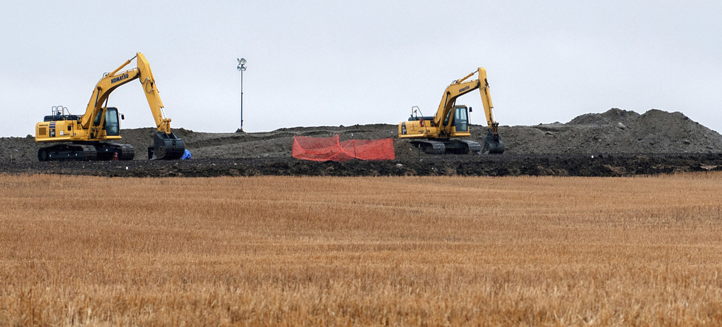 FILE - This Oct. 11, 2013 file photo shows cleanup at the site of a Tesoro Corp. pipeline break that spilled more than 20,000 barrels o...