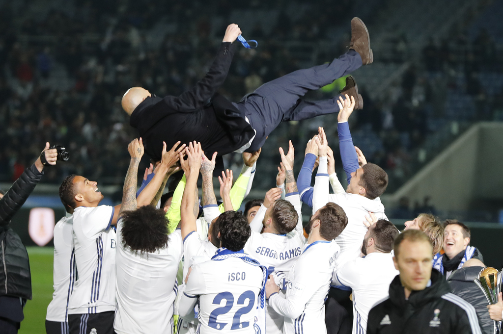 Real Madrid's head coach Zinedine Zidane is tossed into the air in celebration after his team won the final against Kashima Antlers at ...