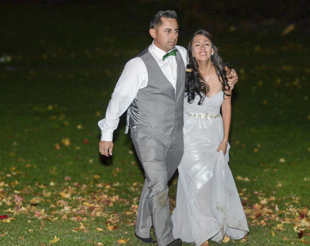 Wedding party members walk away as Los Angeles County Fire Dept. firefighters work at the scene where a large tree fell on a wedding pa...