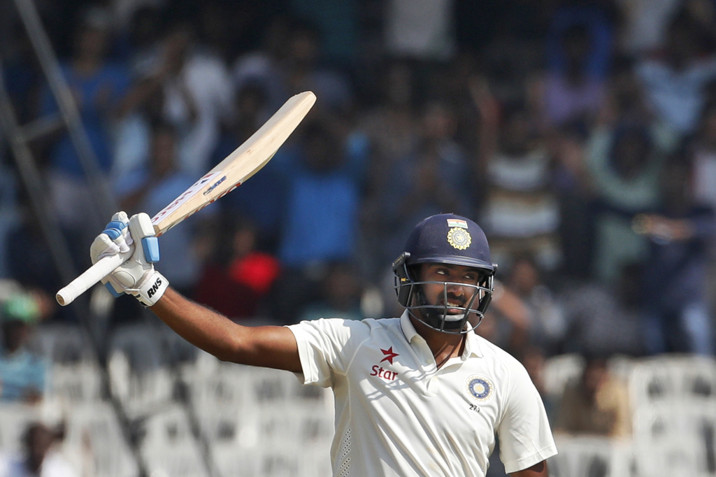 India's Ravichandran Ashwin raises his bat after scoring fifty runs against England during their fourth day of the fifth cricket test m...