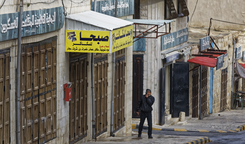 A man stands by shuttered shops opposite Karak Castle in the central town of Karak, about 140 kilometers (87 miles) south of the capita...