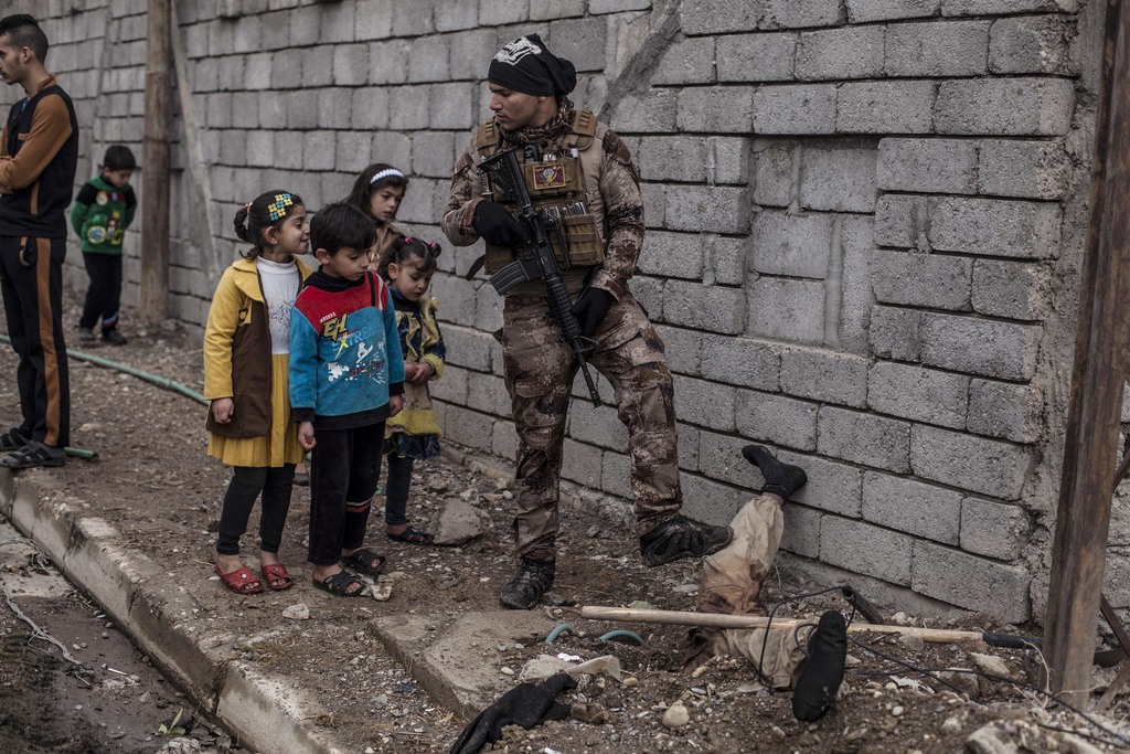 In this Sunday, Dec. 18, 2016 photo, Iraqi children look at the body of a half-buried Islamic State militant while talking to an Iraqi ...