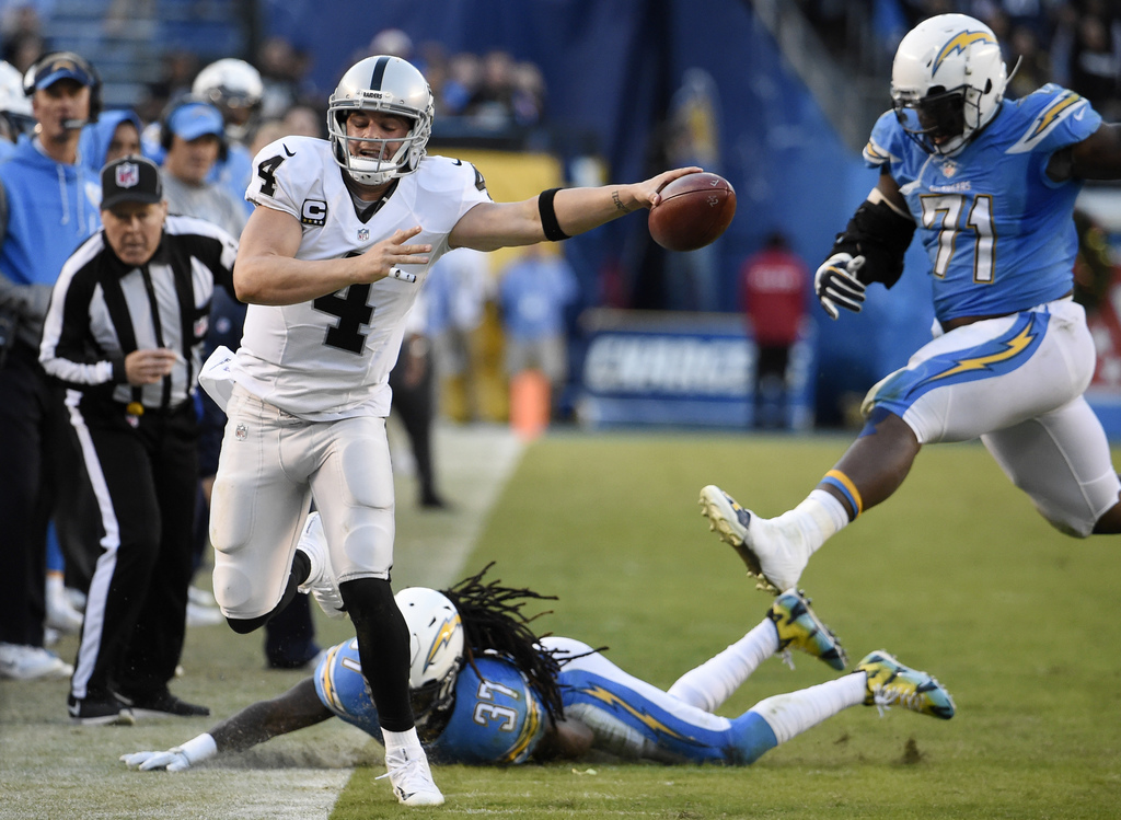 Oakland Raiders quarterback Derek Carr (4) reaches for a first down before going out of bounds as San Diego Chargers strong safety Jahl...