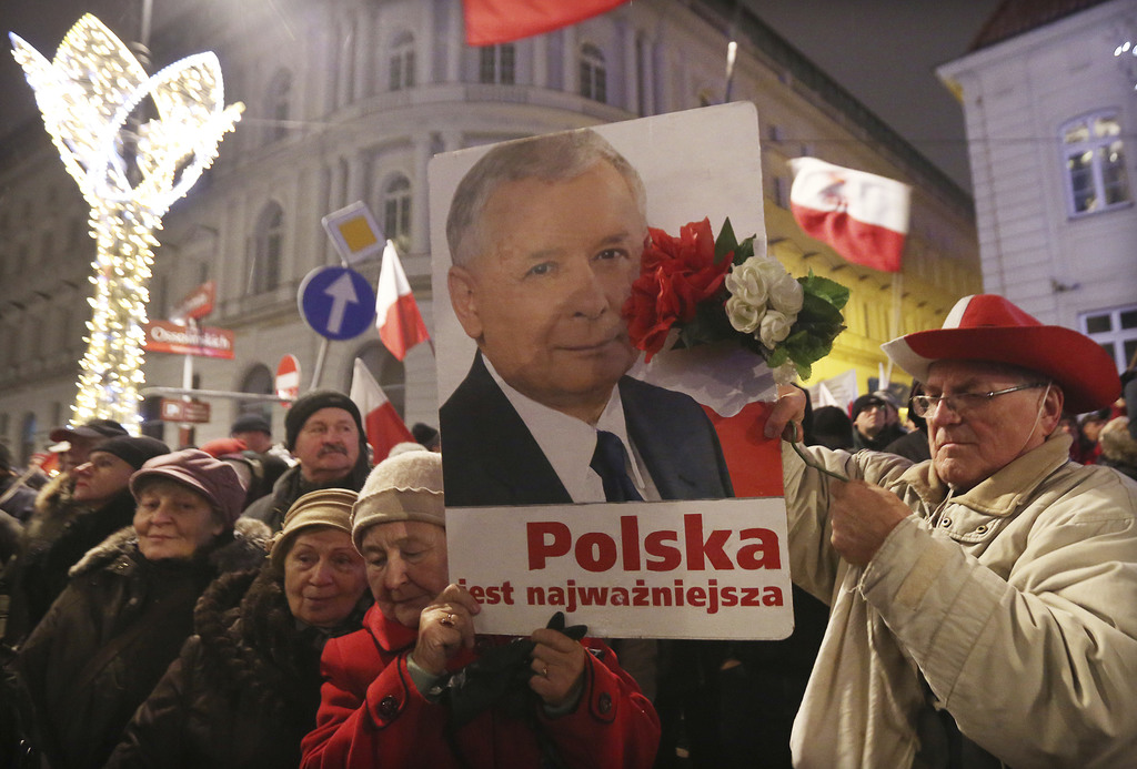 Supporters of the ruling Law and Justice party with a portrait of the leader Jaroslaw Kaczynski as they attend a pro-government rally i...