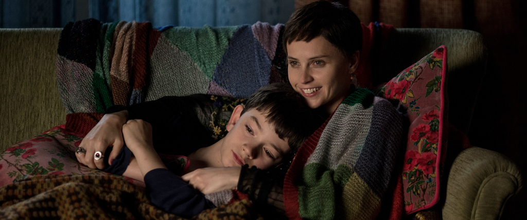 """This image released by Focus Features, Felicity Jones, right, and Lewis MacDougall appear in a scene from """"A Monster Calls."""" (Quim Vive..."""