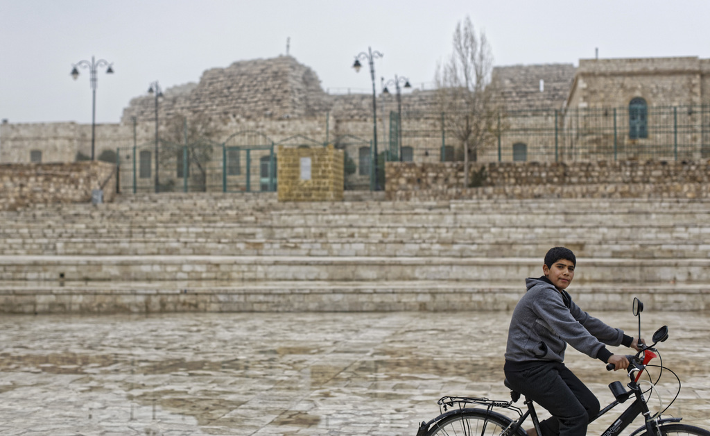 A Jordanian boy rides his bicycle in front of empty steps leading to Karak Castle in the central town of Karak, about 140 kilometers (8...