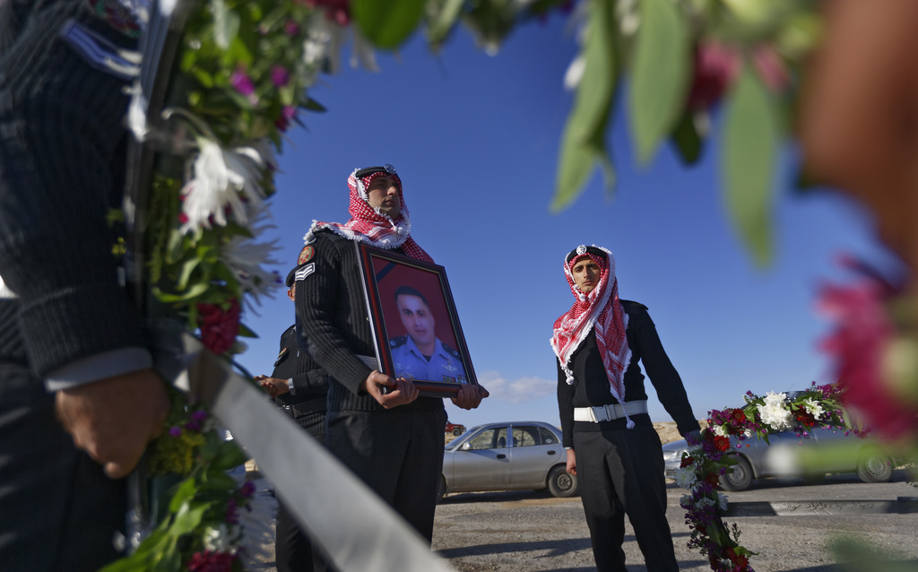 A member of the Jordanian Gendarmerie holds a portrait of his killed colleague Lieutenant Colonel Saed al-Maaytah, as he prepares for t...