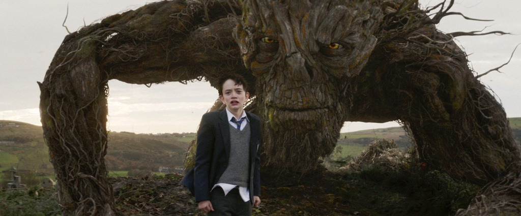 This image released by Focus Features, Lewis MacDougall appears with The Monster, voiced and performed by Liam Neeson, in a scene from ...