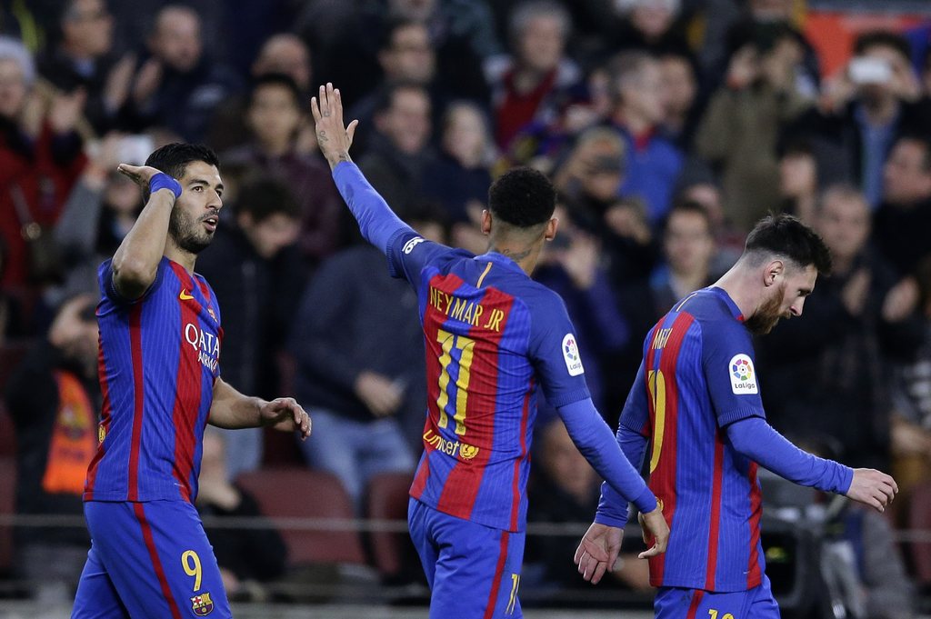 FC Barcelona's Luis Suarez, left, reacts after scoring with his teammate Neymar, center, during the Spanish La Liga soccer match betwee...